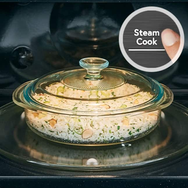A glass dish full of prepared rice with vegetables sits on the convection microwave's turntable.