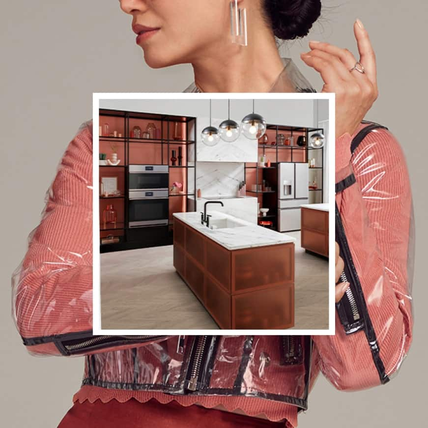 An image of Cafe appliances installed in a modern kitchen is superimposed over a woman dressed in trendy orange clothes that match the cabinets.