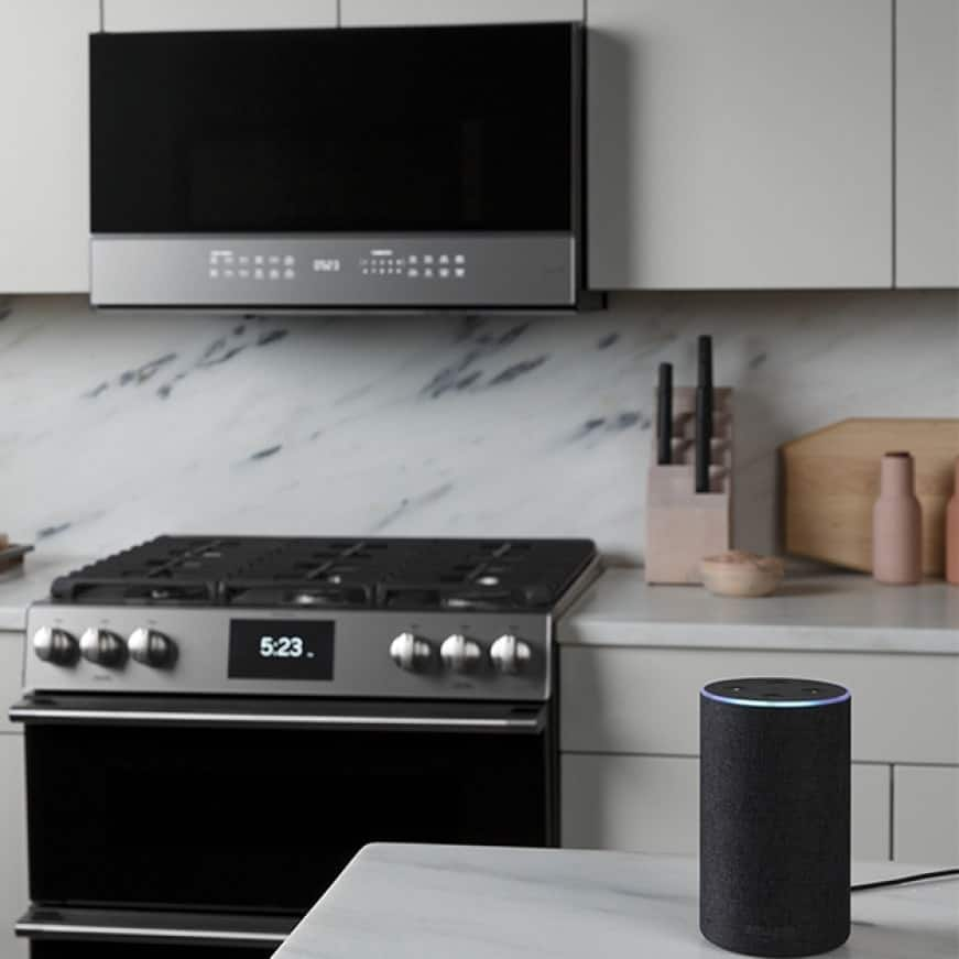A smart home speaker sits on the counter in front of a microwave and range.