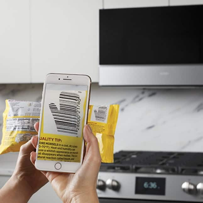 A person holding a phone scans the barcode of a bag of food with their hand.
