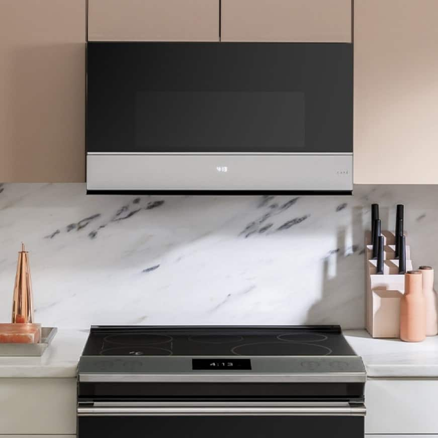 The Cafe microwave installed over a electric range. Modern cabinetry and marble frame the appliances.