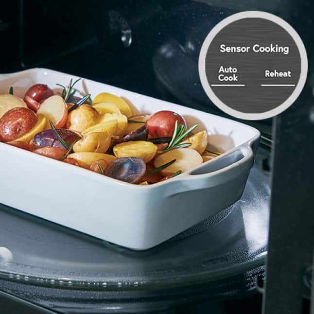 A ceramic dish of assorted potatoes and herbs sit on the turntable of the open convection microwave, ready to heat.