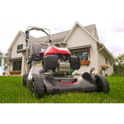 View of the motor, focused on the engine. Shows the mower in front of a house.