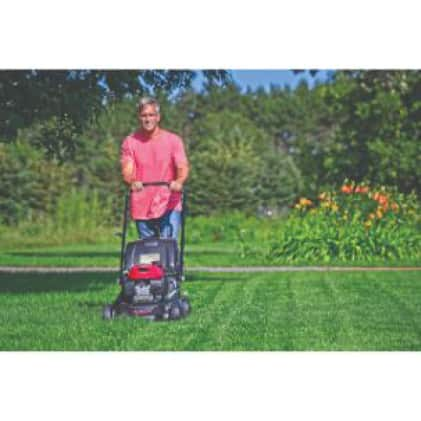 Image of man mowing his lawn.