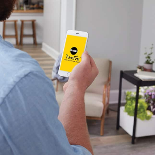 Close up shot of person using the Scotts Miracle-Gro Twelve app on a mobile phone.