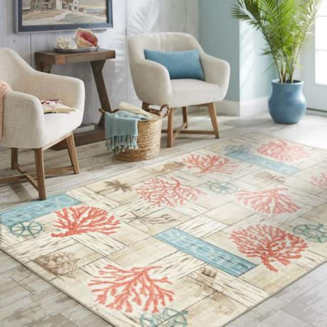 Center of the image is a rug that has images of compasses, coral, beach chairs, and light blue, wooden signs with words like ocean and shore on them.