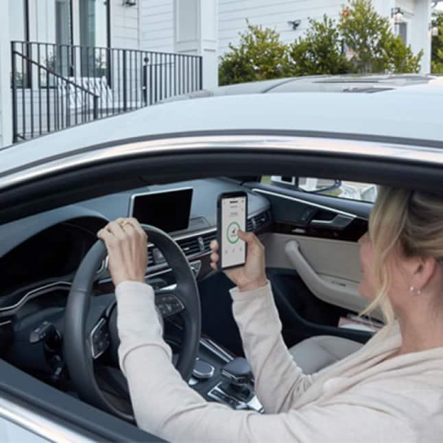 Woman unlocking the door from inside her car using the Kwikset app.