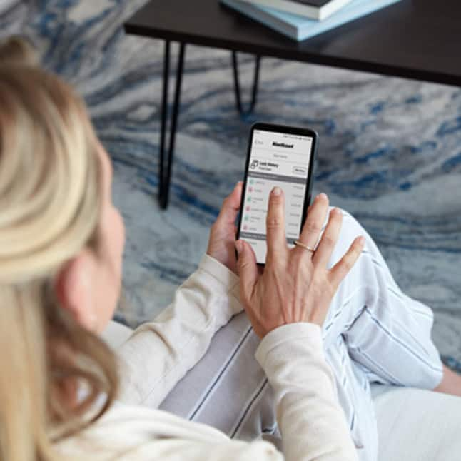 Woman on couch using phone to check lock history on Kwikset app.