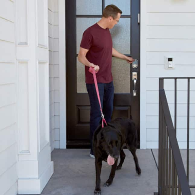Man walking a dog using the lock button on the front door with Aura deadbolt.