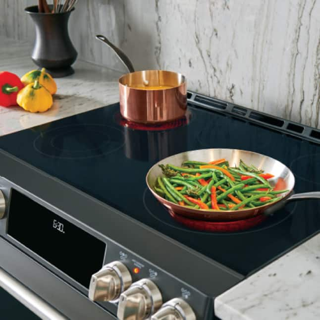 A copper pot of sauce and of mixed vegetables cook on the Cafe range's sleek black glass cooktop.The burners underneath glow red with heat.