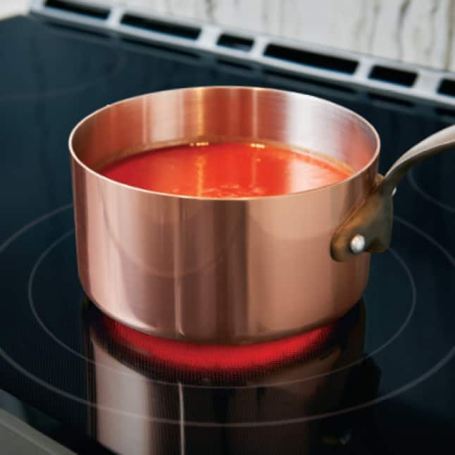 A closeup of a pot of sauce on a burner.Rings marked on the glass indicate the sizes of the burners as the element glows red with heat.