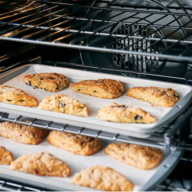 Two sheets of golden-brown scones bake on separate racks of the oven.The convection fan has just stopped and the oven light is turned on.