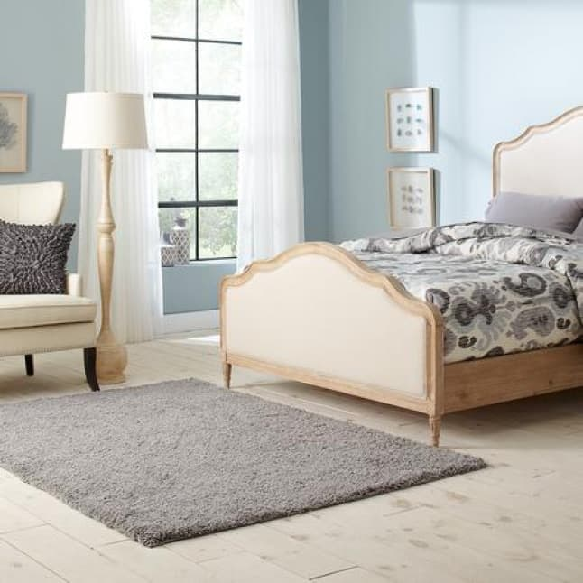 A tufted, solid, grey shag rug sits in front of a queen size bed.