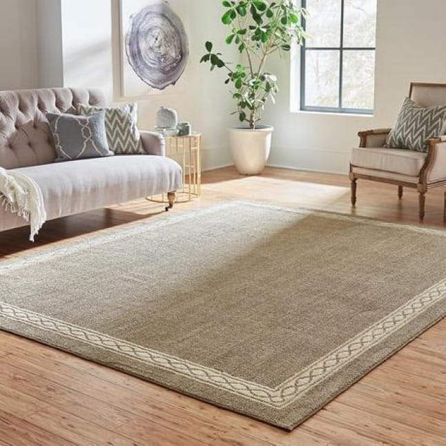 There is a two-tone, neutral rug with an interlocking chain border design laying in the center of the room on hardwood floor.