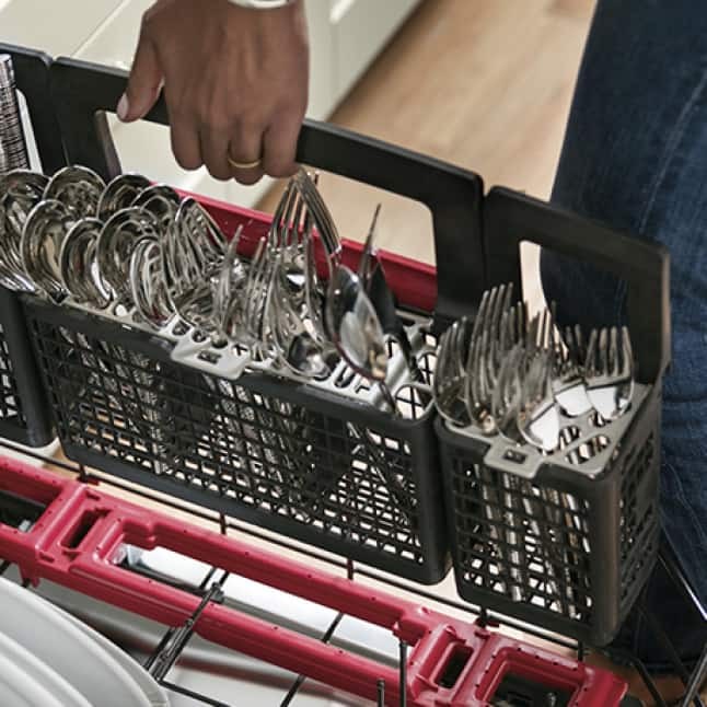 A hand places the dishwasher's filled silverware basket into its place over the jets
