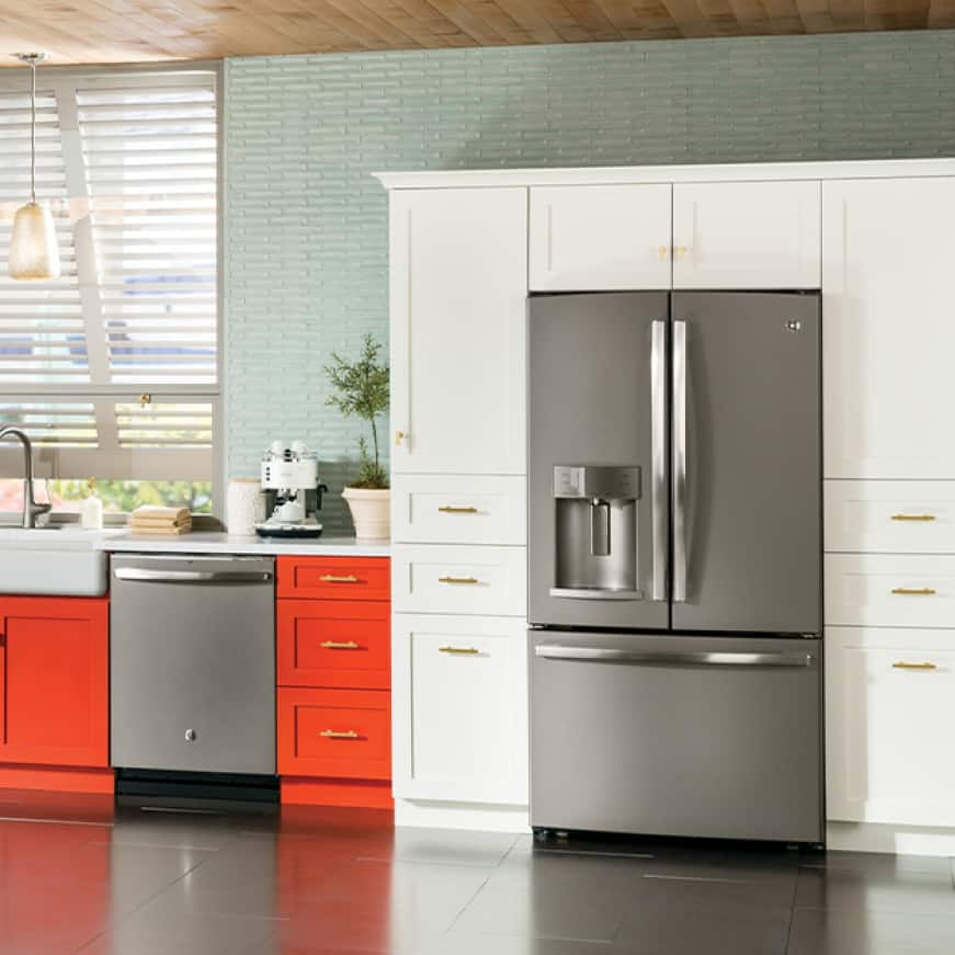 Adora appliances are installed in a modern and colorful kitchen. The slate finish of the appliances stand out against the orange and white cabinetry.