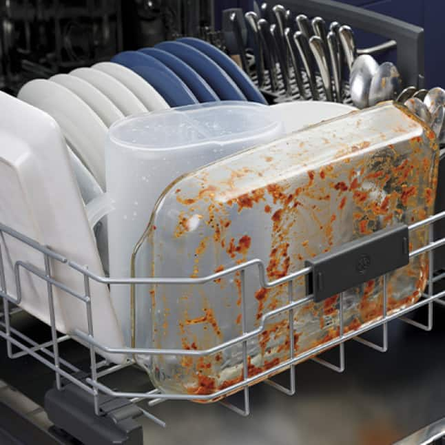 Dirty dishes are all neatly stacked into the dishwasher's lower drawer, ready to clean.