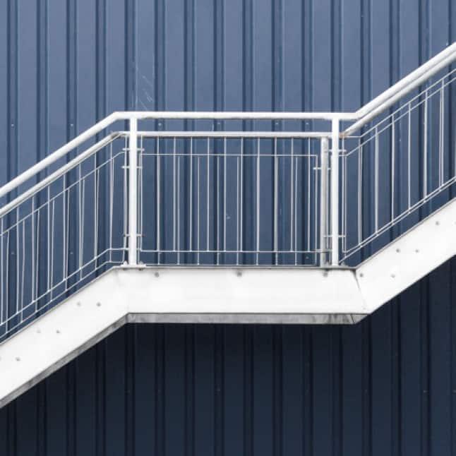 Exterior white metal stair railing against metal wall painted blue