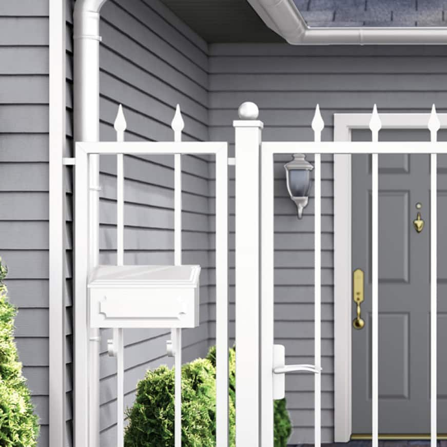 Front of house with metal gate and garage door painted white