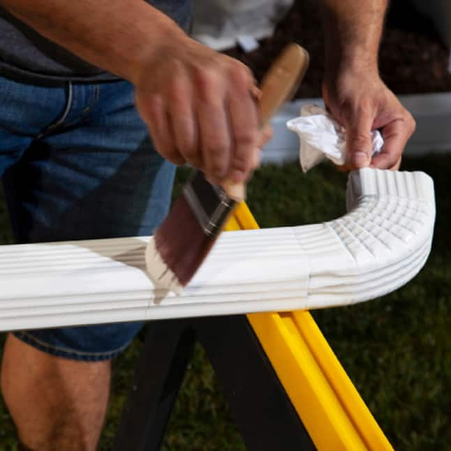 White paint being brushed onto metal gutter