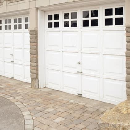 White garage door shown against masonry house