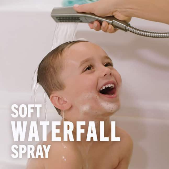 Images is of a smiling child in a bathtub with his hair being gently rinsed by a soft waterfall spray coming out of the hand shower