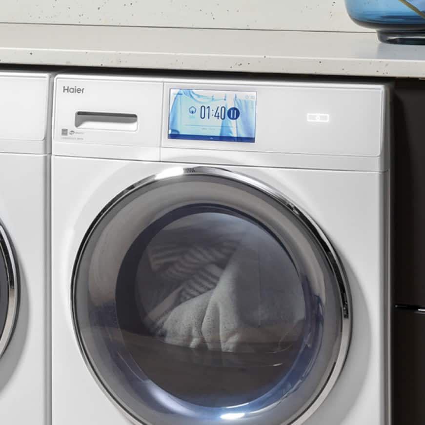 Close up of the dryer displaying the LCD touch screen and clothes tumbling in the Haier dryer