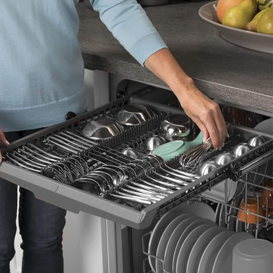 A hand pulls out the upper rack from the top of the dishwasher. Various small cookware and utensils are held by the rack.