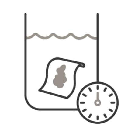 An icon of a tub. A soiled cloth is submerged in water, and a clock superimposed in the corner designates  time to soak off the stain.