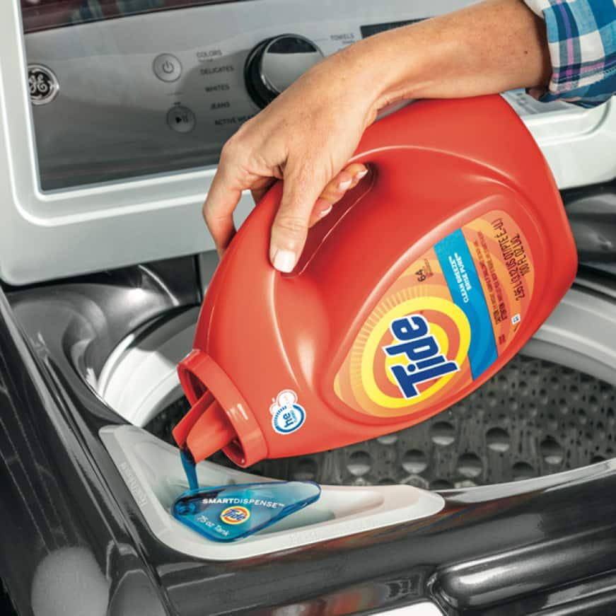 Hand pouring a bottle of Tide detergent into the SmartDispense detergent tank