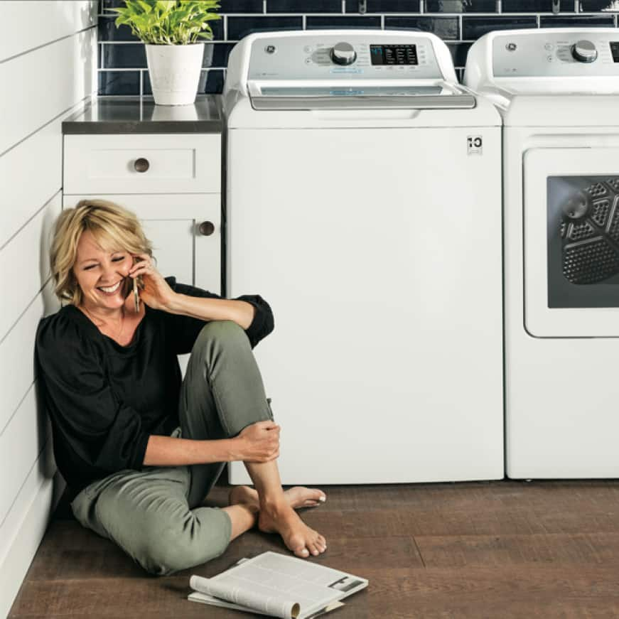 Woman sitting next to quiet washer reading a magazine while on the phone