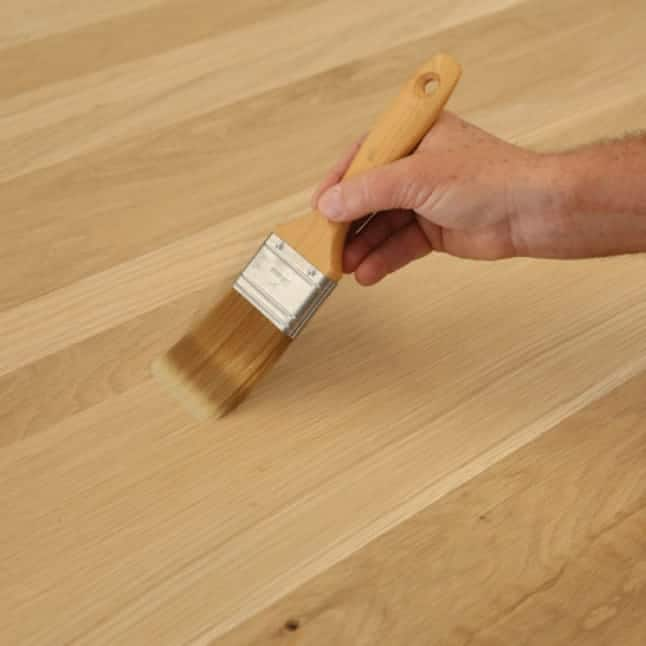 A hand brushing pre-stain conditioner on a wood substrate.