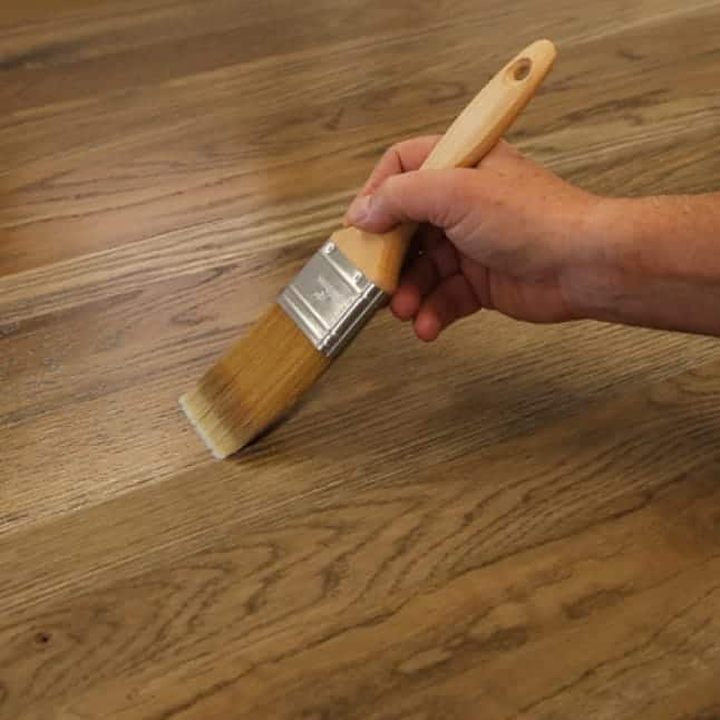 A hand brushing polyurethane on a wood substrate.