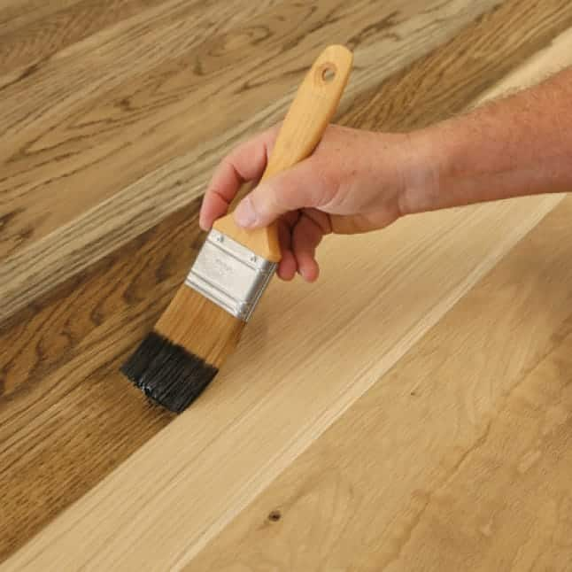 A hand brushing stain on a wood substrate.