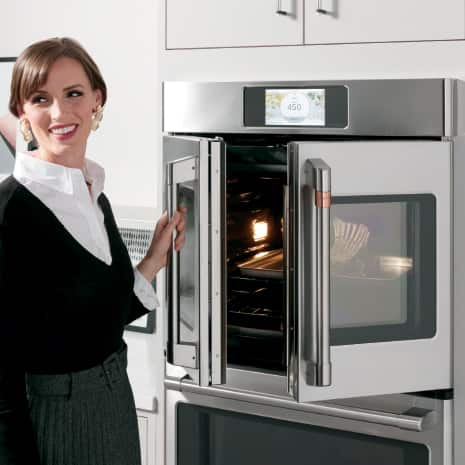 Angled shot of woman opening French-door wall oven with food cooking inside
