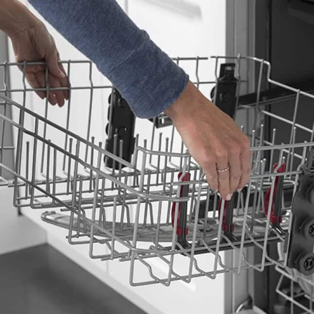 A woman grabs both sides of the top rack, adjusting the rack to make space.
