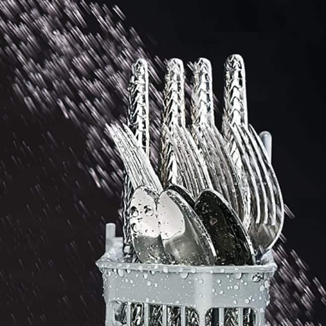Water jets splash a basket of silverware with a powerful stream of water