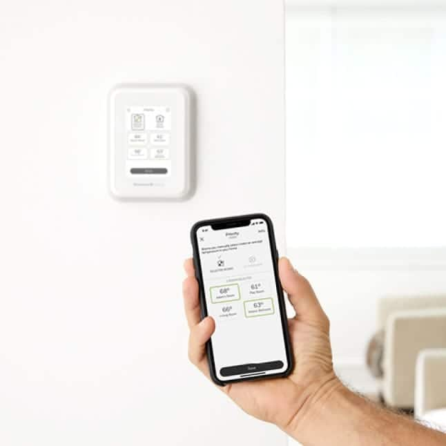 Thermostat and smartphone displaying multi-room options