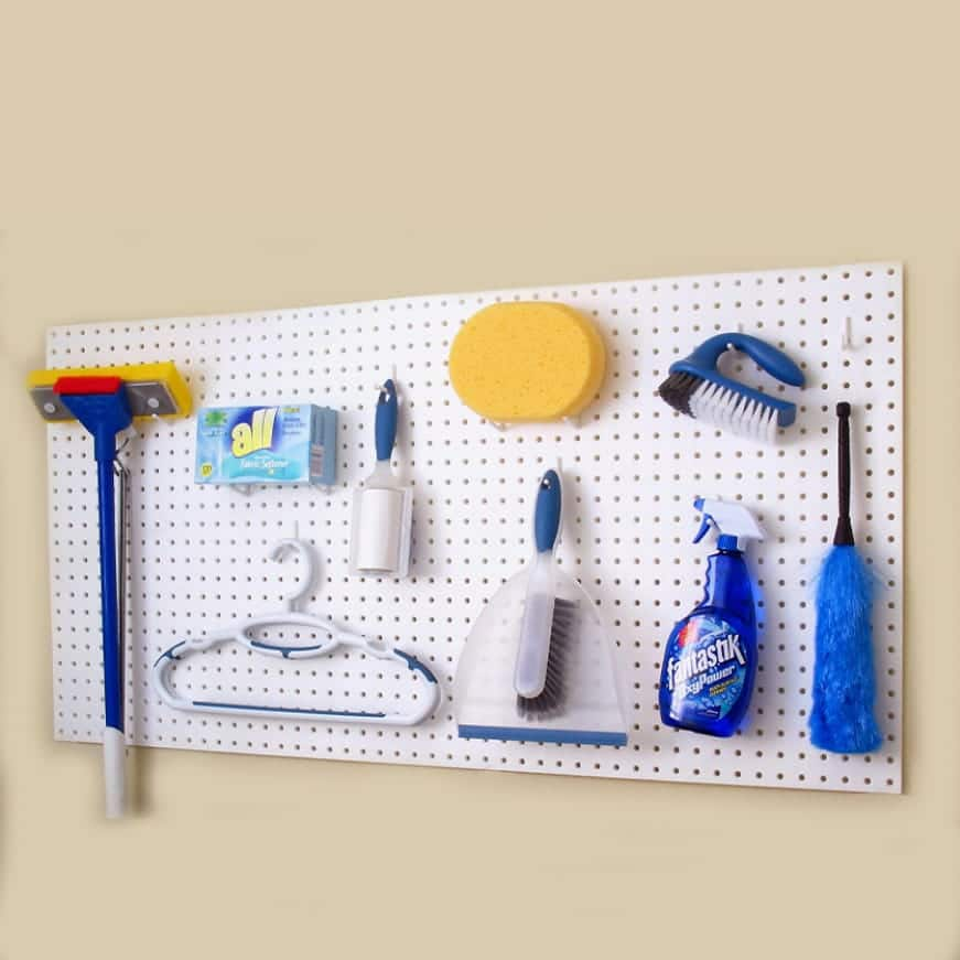 White pegboard holding cleaning supplies