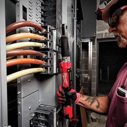 Electrician with work gloves, safety glasses, and a hard hat on uses an M12 FUEL digital torque wrench.