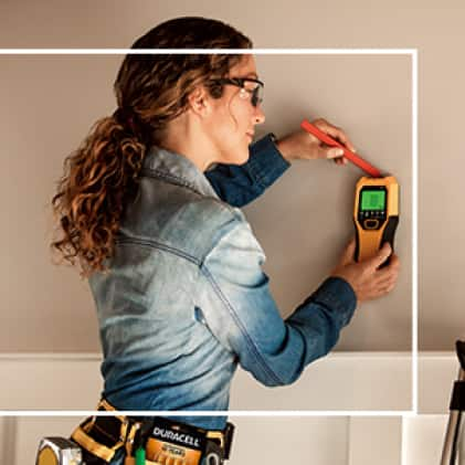 Contractor using battery powered stud finder