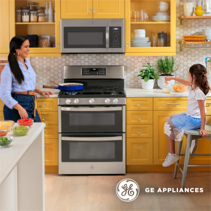 Lifestyle image of woman and young girl cooking near a free-standing range with GE Appliances logo appearing in the bottom right corner