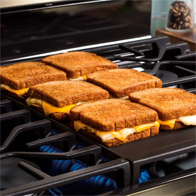 6 grilled cheese sandwiches cooking on a center griddle
