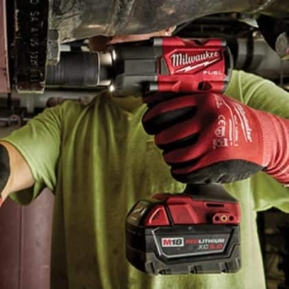 "Man wearing work gloves uses an M18 FUEL 1/2"" Mid-Torque Impact Wrench to remove a large bolt."