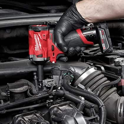 A man uses an M18 FUEL 3/8 Stubby Impact Wrench to remove a stubborn fastener in  a confined workspace.