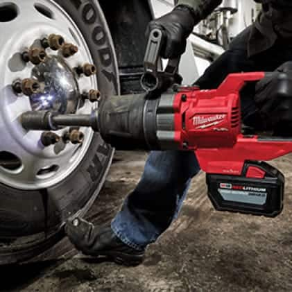 Professional using M18 FUEL D-Handle High Torque Impact Wrench to fasten car lug nut.