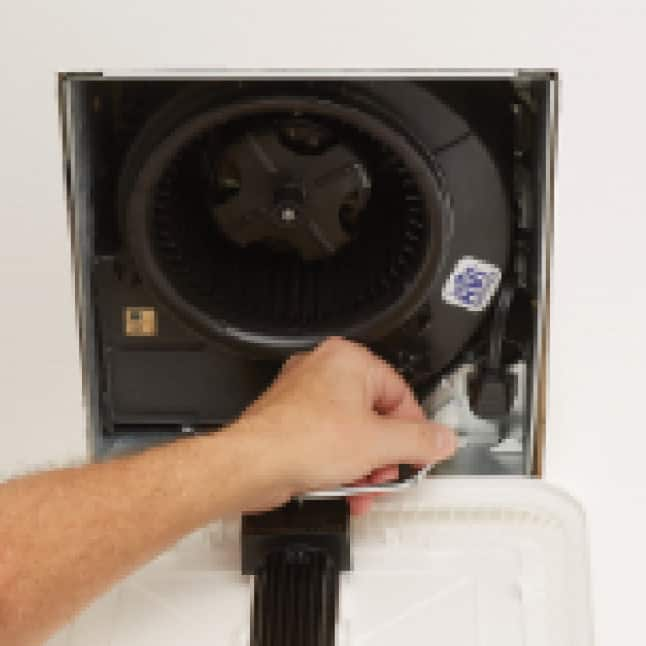 Image of the grille open to reveal the fan housing and a hand plugging in the EZDUCT connector.