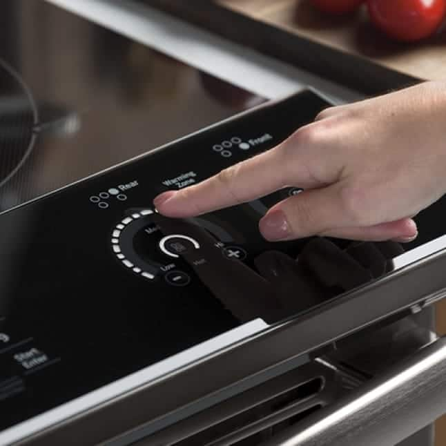 A finger swipes the controls on the front panel of the range