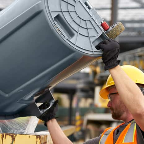 Man using built-in handle to lift and dump container