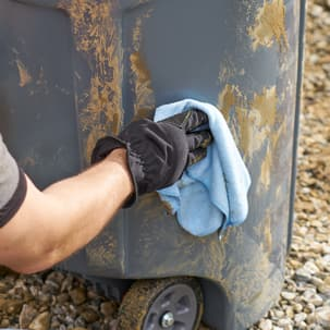 Man using microfiber cloth to wipe off dirty container